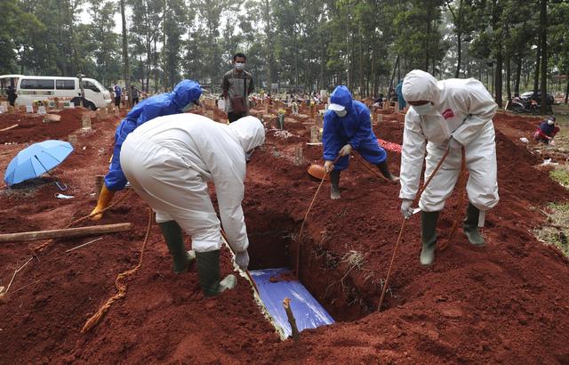 Det er rapportert flere koronadødsfall i Indonesia, Myanmar og Malaysia nå enn det ble rapportert i India på det verste. Her blir en av de omkomne i Indonesia gravlagt. Foto: Achmad Ibrahim / AP / NTB