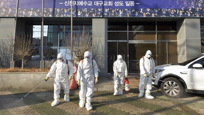 Helsearbeidere sprayer desinfiserende stoff foran en kirke i den sørkoreanske byen Daegu. Byens ordfører oppfordrer byens 2,5 millioner innbyggere til å holde seg innendørs.