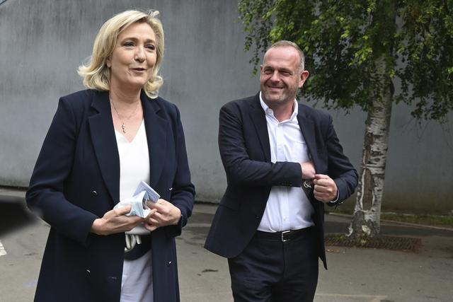 Marine Le Pen sammen med sin partifelle Steeve Briois etter å ha avlagt stemme i Henin-Beaumont i Nord-Frankrike søndag. Foto: AP / NTB