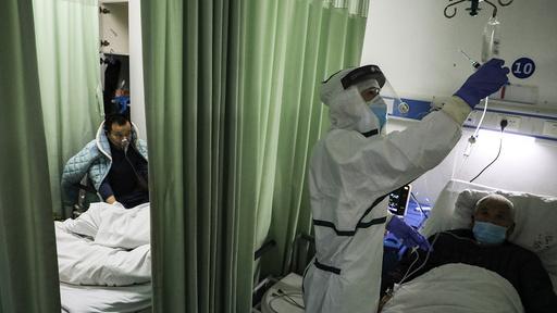 En sykepleier ser til en pasient på isolatavdelingen på et sykehus i Wuhan, byen der viruset først ble registrert.