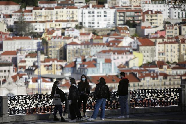 En gruppe yngre mennesker har på seg munnbind i Lisboa i Portugal. Foto: Armando Franca / AP / NTB