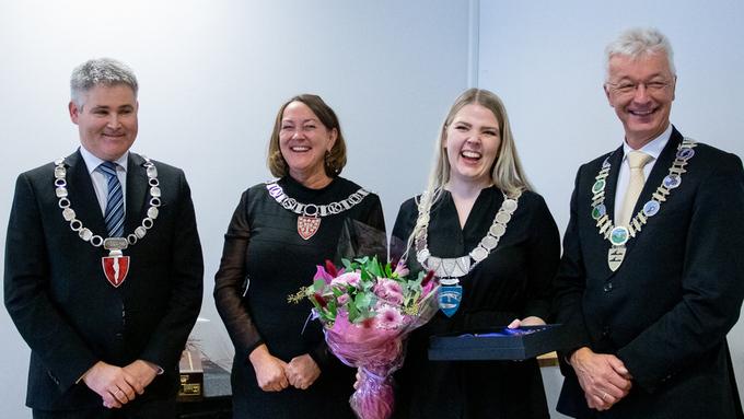 NY ORDFØRAR: Øyvind Oddekalv (f.v.), Astrid Aarhus Byrknes og Jon Askeland (t.h.), overrekte orførarkjede og klubbe til den første ordføraren i Alver; Sara Hamre Sekkingstad.