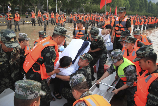 Kinesisk militærpersonell evakuerte torsdag innbyggere fra et sykehus der rundt 3000 mennesker var fanget av vannmassene i millionbyen Zhengzhou. Foto: Chinatopix Via AP / NTB