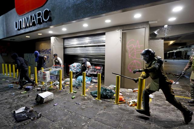 Politiet forsøker å arrestere folk som plyndrer et supermarked i Santiago, men de viktigste demonstrasjonene gikk fredelig for seg. Foto: Luis Hidalgo / AP / NTB