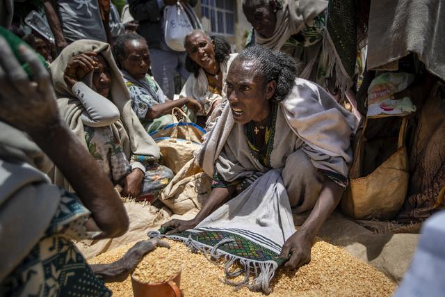 En etiopisk kvinne diskuterer fordelingen av gule bønner i byen Agula i Tigray-regionen i Etiopia, den 8. mai i år. Norge øker støtten til området, som er rammet av en stadig voksende sultkrise. Foto: Ben Curtis / AP / NTB scanpix