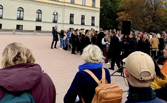Folk venter på å få hilse de nye statsrådene på Slottsplassen. Finansminster Trygve Slagsvold Vedums kone og to døtre står helt fremst i køen.