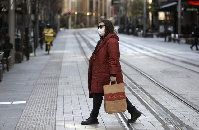 En enslig kvinne krysser en handlegate som normalt er en av Sydneys travleste. Nå sier delstatsregjeringen at koronautbruddet i storbyen er en nasjonal krise. Foto: Rick Rycroft / AP / NTB