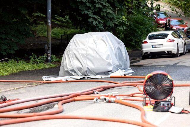 Brannvesenet har lagt et teppe over bilen.