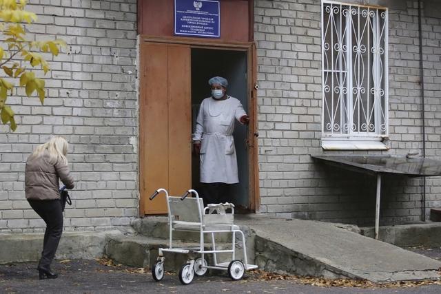 En helsearbeider tar imot en pasient på et sykehus i russisk-kontrollerte Donetsk i Ukraina. I Donetsk-regionen er det registrert over 1.000 nye koronasmittede og 100 dødsfall siste døgn. Foto: Alexei Alexandrov / AP / NTB