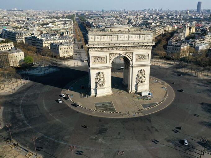 Rundkjøringen rundt Triumfbuen i Paris var denne uken nesten tom for biler. Tross portforbudet øker dødstallene i Frankrike drastisk.