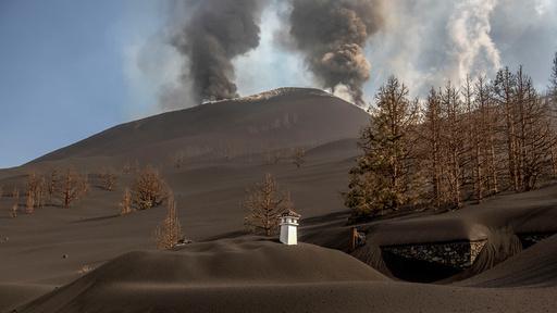 Bare pipen stikker opp av asken som dekker dette huset på La Palma. I bakgrunnen ses vulkanen Cumbre Vieja som har hatt utbrudd i fire uker.