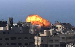 Røyk og flammer stiger opp etter et israelsk luftangrep mot en bygning i Gaza by fredag. Foto: Hatem Moussa / AP / NTB