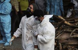 Pårørende sørger over sine kjære ved likbål i India. Foto: AP / NTB