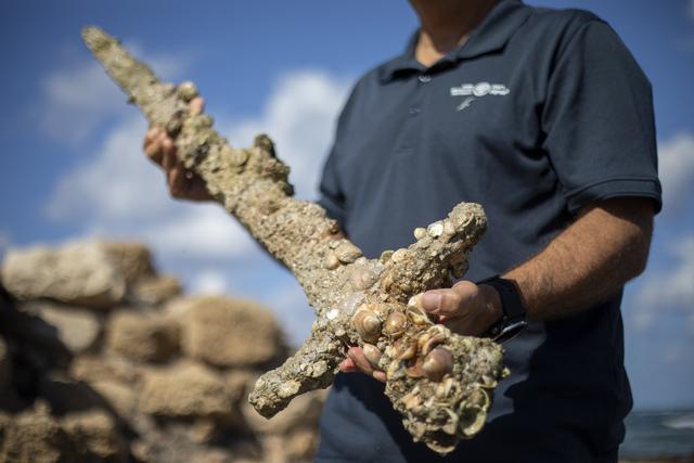 Et sverd med en lengde på én meter ble funnet ved kysten av Israel i helgen. Leder Jacob Sharvit i senteret for marin arkeologi holder sverdet. Foto: AP / Ariel Schalit / NTB