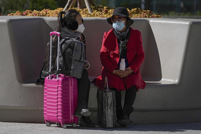 To kvinner med munnbind utenfor et kjøpesenter i Beijing. Foto: Andy Wong / AP / NTB