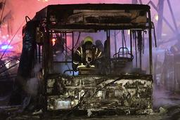En brannmann slukker en buss i Tel Aviv som ble truffet av en rakett sendt fra Gazastripen. Foto: Avshalom Sassoni / AP / NTB