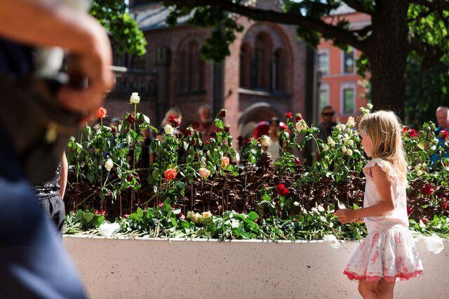 Flere la ned blomster ved 22. juli-minnesmerket utenfor Oslo domkirke i dag.