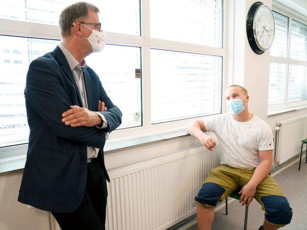 Helsebyråd i Oslo, Robert Steen (til v.), i samtale med Bendik Gropen, som fikk vaksine.