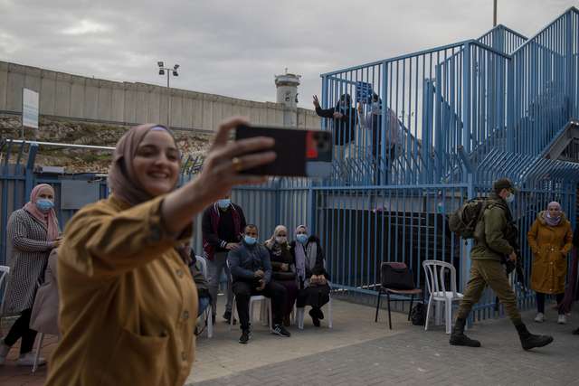 Palestinere tar bilder etter å ha fått koronavaksine fra et israelsk helseteam ved militærposten i Qalandia på den okkuperte Vestbredden i februar. Arkivfoto: Oded Balilty / AP / NTB