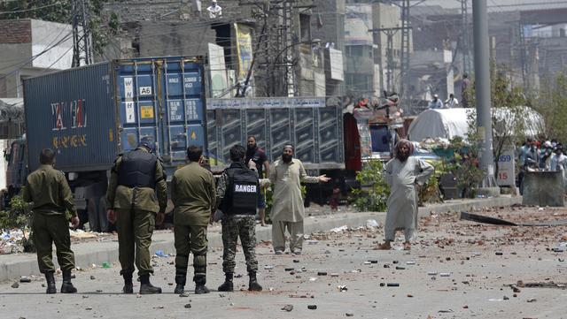 TPL-støttespillere, som blokkerer en vei i Lahore, snakker med politifolk søndag.