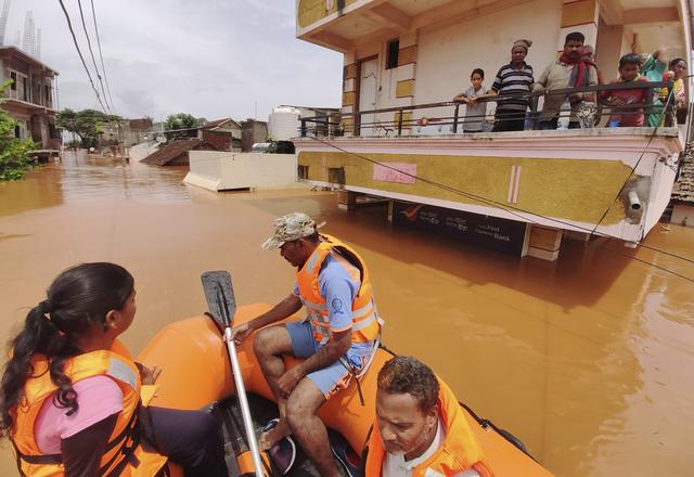 Gummibåter må brukes for å evakuere strandede innbyggere i Kolhapur i den indiske delstaten Maharashtra, der kraftig monsunregn har ført til storflom. Foto: AP / NTB