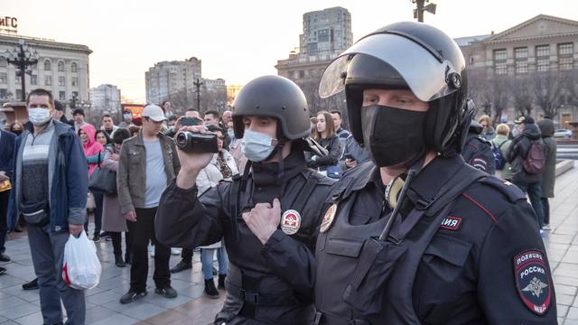 En russisk politibetjent filmer folk i forkant av demonstrasjoner til støtte for opposisjonsleder Aleksej Navalnyj i byen Khabarovsk onsdag. Nesten 200 skal være pågrepet, og det er ventet større demonstrasjoner i Moskva og St. Petersburg utover ettermiddagen. Foto: Igor Volkov / AP / NTB