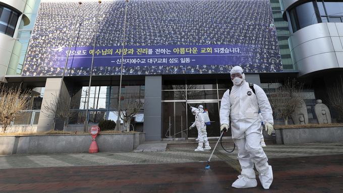 En mann i beskyttelsesdrakt sprayer desinfiserende væske foran kirken til Shincheonji-sekten i Daegu i Sør-Korea.