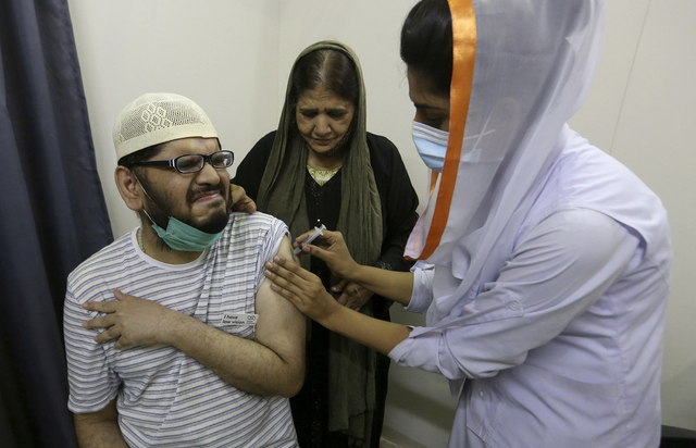 En mann reagerer når han får en dose med den kinesiske Sinovac-vaksinen. Han er en av flere millioner i Pakistan som har fått minst én dose koronavaksine. Foto: AP / NTB