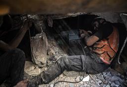 Palestinske redningsarbeidere leter etter overlevende i ruinene av en bygning som ble ødelagt i et israelsk luftangrep søndag. Foto: Khalil Hamra / AP / NTB
