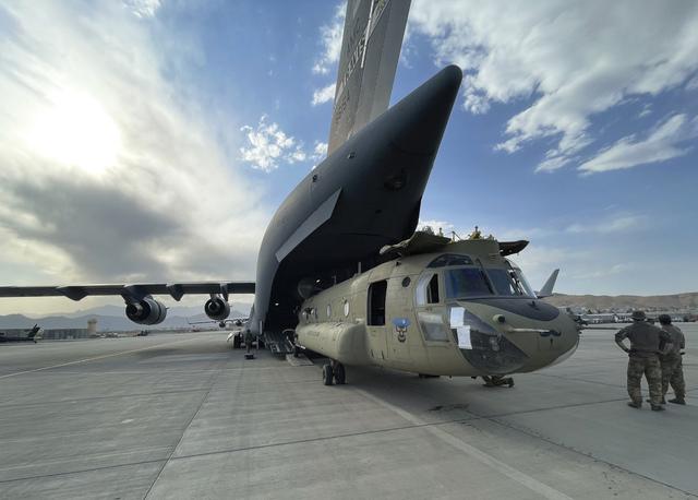 Et Chinook-helikopter blir lastet om bord et C-17 Globemaster-transportfly før amerikanerne forlot Afghanistan. Det amerikanske militæret uskadeliggjorde og etterlot flere titall militærfly og pansrede kjøretøy før de forlot Afghanistan. Foto: Pentagon via AP / NTB
