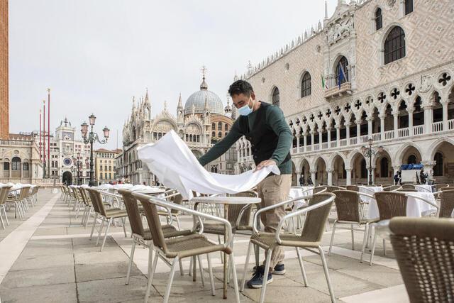 En kelner dekker på bord på en restaurant på Markusplassen i Venezia. Italia lemper nå på karantenekravene.