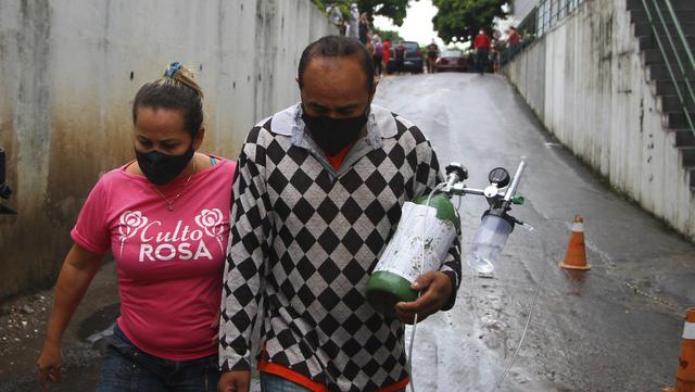 En mann og kona hans bærer en oksygentank til svigermoren sin, som er innlagt på sykehus med covid-19.