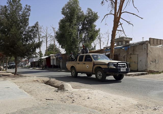 Afghanske sikkerhetsfolk patruljerer en forlatt gate i Lashkar Gah tirsdag. I andre deler av byen pågår harde kamper mellom regjeringsstyrker og Taliban. Foto: Abdul Khaliq / AP / NTB
