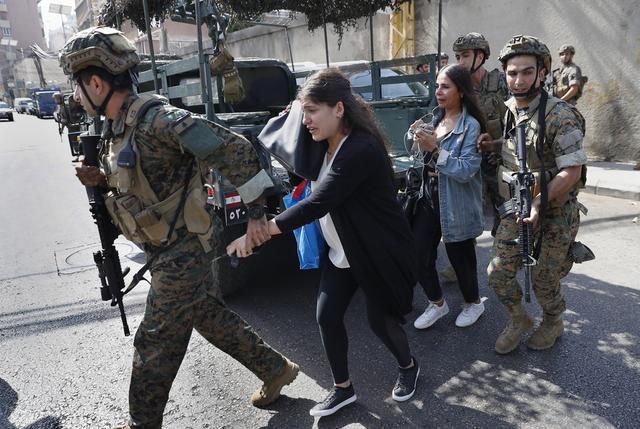 Libanesiske soldater eskorterer lærere bort fra skolen de jobber på under torsdagens gatekamper, som skjedde like ved frontlinjen i Beirut under den 15 år lange borgerkrigen. Foto: Hussein Malla / AP / NTB