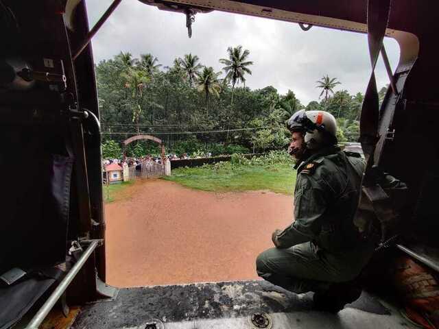 Et redningshelikopter leter etter flom- og skredrammede i Kottayam-distriktet sørvest i India, som siden fredag har blitt rammet av kraftige regnvær. Foto: Den indiske marinen / AP / NTB