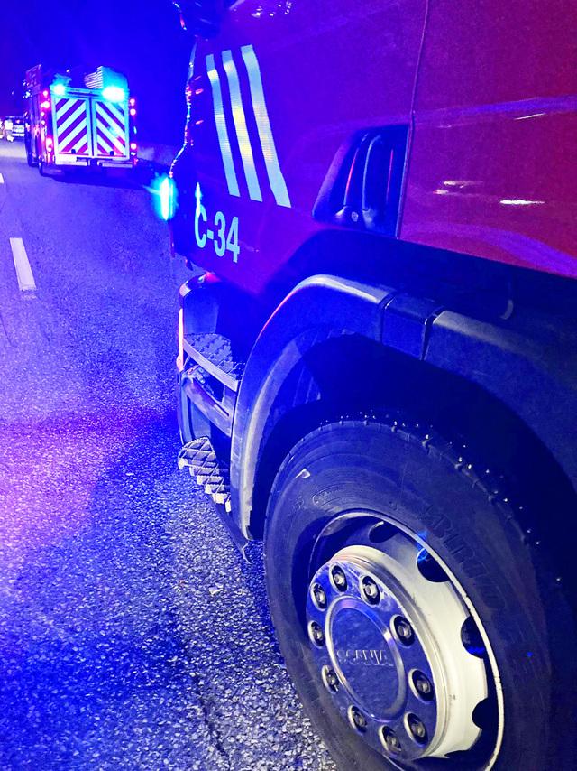 En brannbil med en brannkonstabel på taket ble påkjørt av en bil da den sto i sperring ved kjedekollisjon på E18 i sørgående før Hemtunnelen. Foto: Vestfold Interkommunale Brannvesen / NTB