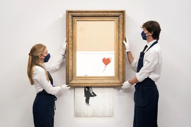 Det delvis ødelagte verket fra artisten Banksy, «Love is in the Bin», er solgt for 18,6 millioner pund. Det er ny prisrekord for et Banksy-. verk. Foto: Dominic Lipinski / PA / AP / NTB