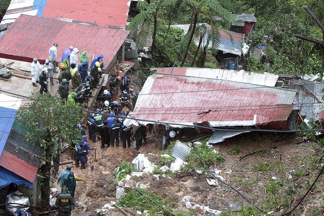 Redningsmannskap leter etter ofre i et hus som ble tatt av jordskred i Baguio tirsdag. Foto: AP / NTB