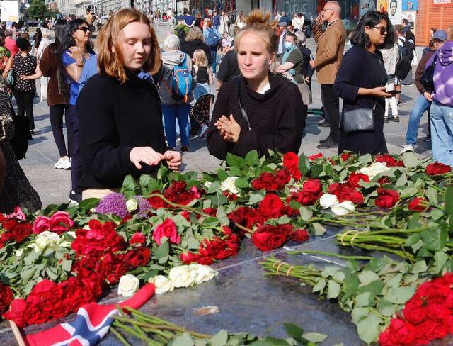 Synne Syslak (til v.) og Oda Hausberg la ned blomster på Den blå steinen under minnemarkeringen.