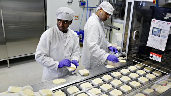 Lawrence Lawton og Benedict Jude pakker porsjonspakker med ferdig skivet ost.