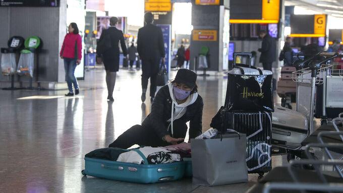 En kvinne pakker kofferten sin på Heathrow flyplass etter at det 29. januar ble klart at British Airways kansellerte alle flyvninger til og fra Kina. Nå får viruset konsekvenser, både for flere flyselskaper og reisebyråer.