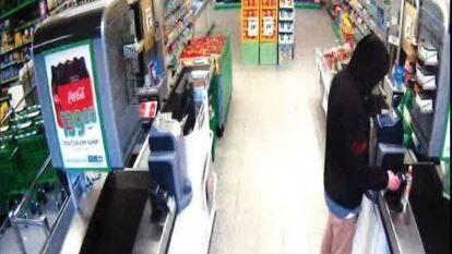 Her skal mannen ta ut penger med et stjålet bankkort i en butikk.