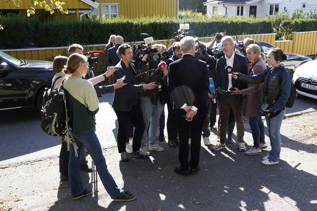 Ap-leder Jonas Gahr Støre, med ryggen til, omgitt av pressefolk utenfor sin bolig, dagen etter stortingsvalget som la grunnlag for at han trolig blir statsminister i en kommende regjering. Foto: Terje Bendiksby / NTB