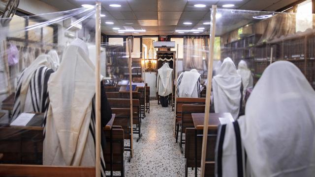 Ultraortodokse jøder i en synagoge i Bnei Brak i Israel. Plastvegger er satt opp mellom de troende for å unngå smittespredning.
