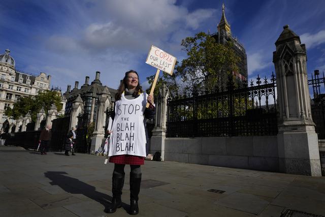 En enslig klimademonstrant holder opp en plakat utenfor parlamentsbygningen i London. Søndag åpner klimatoppmøtet COP26 i Glasgow. Foto: Kirsty Wigglesworth / AP / NTB