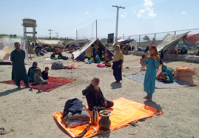 Afghanske familier sitter utenfor teltene sine på pakistansk side av grensen ved Chaman. Nå stenges grenseovergangen inntil videre, mens Pakistan sier landet ikke kan takle en ny flyktningstrøm fra nabolandet. Foto: Jafar Khan / AP / NTB