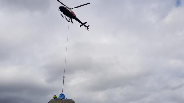 Et helikopter heiser bort det gamle utstyret.