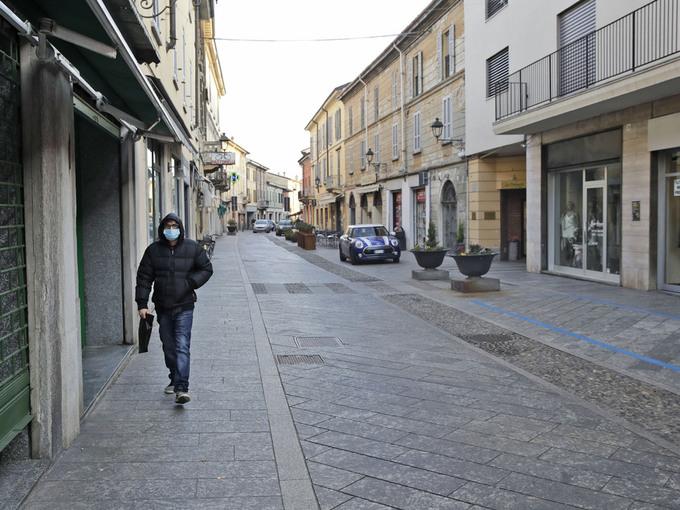 En mann med maske går på gaten i byen Codogno i Nord-Italia.