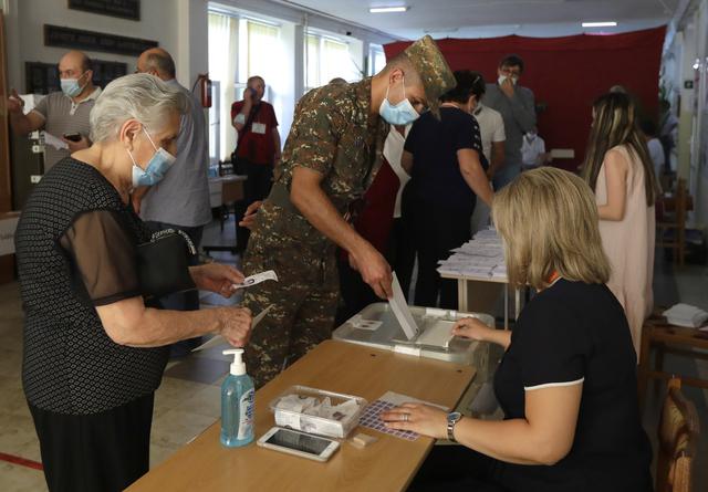 Stemmegivning i et valglokale i Armenias hovedstad Jerevan søndag morgen. Foto: Sergej Grits / AP / NTB