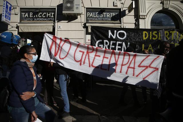 Demonstranter marsjerer i Roma mot det såkalte grønne passet, som skal sikre at alle arbeidstakere enten er vaksinert, har testet negativt for korona eller er blitt friske etter covid-19 før de slipper inn på egen arbeidsplass. Foto: Cecilia Fabiano / LaPresse via AP / NTB